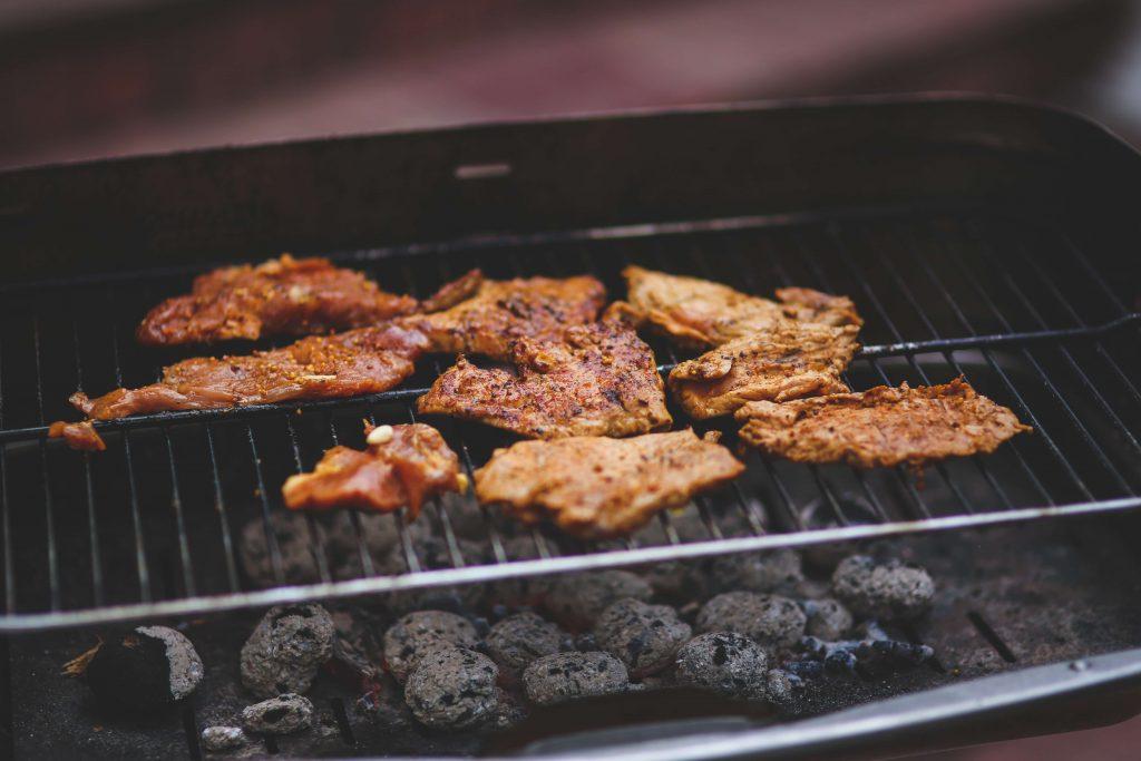 Auf einem Grillrost liegt Fleisch das in Verbindung mit dem Vitamin B12 gebracht wird
