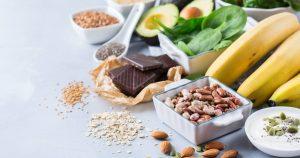 Lebensmittel wie Nüsse, Hülsenfrüchte, Avocado, Spinat, Bananen und dunkle Schokolade sind auf einem Tisch verteilt