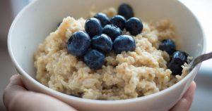 Eine Schale mit Porridge garniert mit Blaubeeren