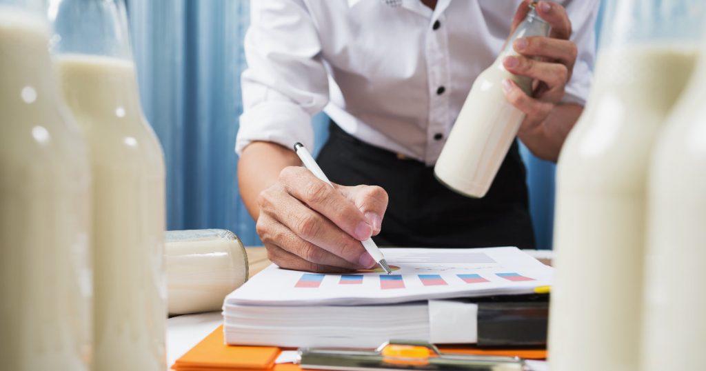 Tiermilch in Flaschen abgefüllt und bei der Kontrolle in einem Labor. Ein Mann trägt Werte in Statistiken ein