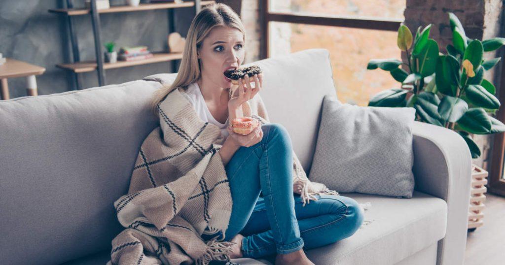 Frau sitzt in eine Decke gehüllt mit je einem Donut in der Hand auf dem Sofa und kämpft gegen Depressionen