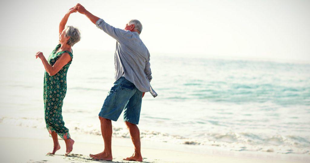 ein älteres Ehepaar tanzt am Strand und ist glücklich in Bewegung