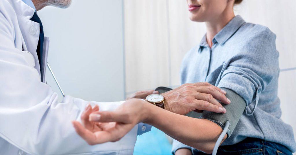 Ein Arzt misst bei einer Patientin den Blutdruck mit einem Blutdruckmessgerät