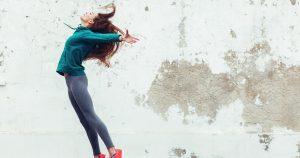 Eine junge fitte Frau springt in die Luft und streckt ihren gesamten Körper aus