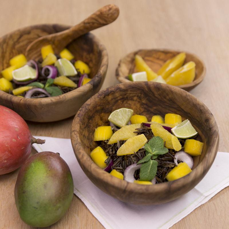 Zwei Schüsseln mit schwarzem Reis und Mango stehen zubereitet auf einem Tisch. Daneben liegen zwei Mangos und eine kleine Schale mit geschnittener Mango.