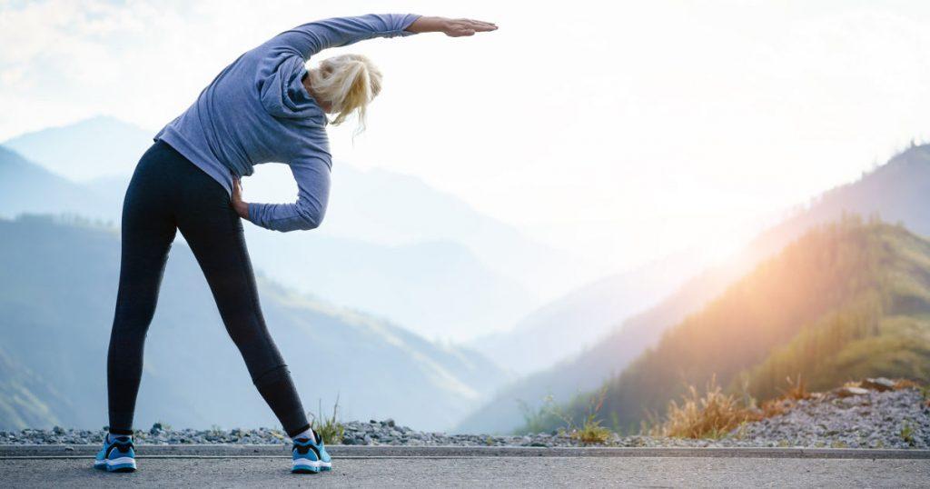 Eine Joggerin steht auf einem Berg und beugt ihren Oberkörper im Stehen zur rechten Seite