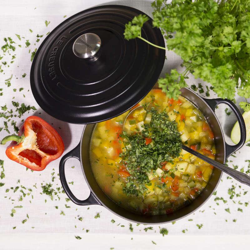 Ein Topf mit bunter Minestrone steht auf einem Tisch. Neben ihm steht ein Strauch Petersilie und eine halbe Paprika aufgeschnitten.