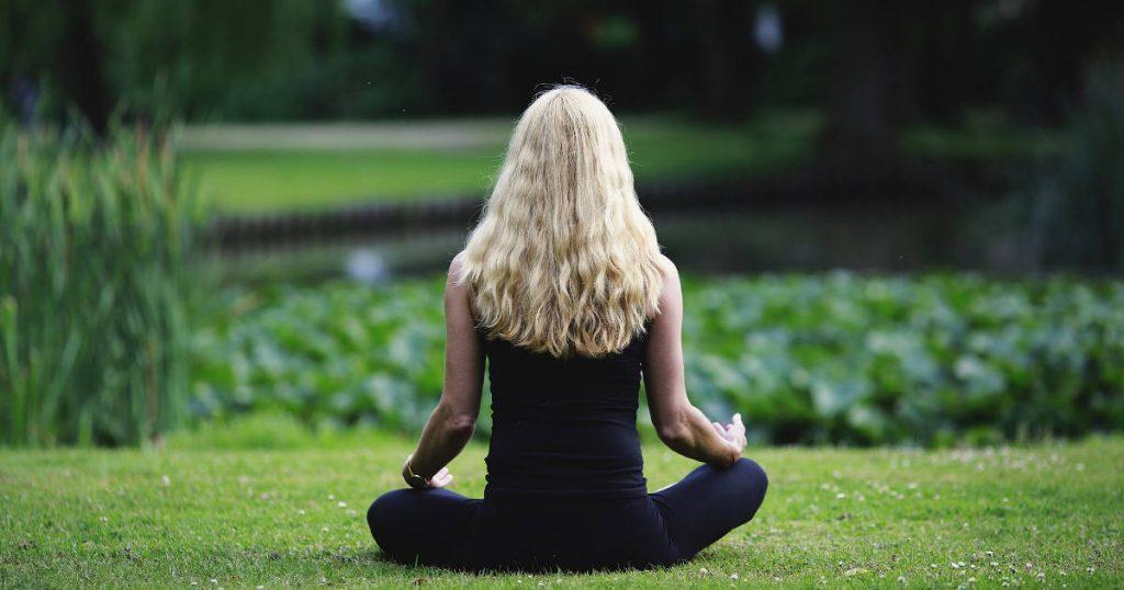 Eine Frau sitzt meditierend auf einer Wiese vor einem Seerosenteich
