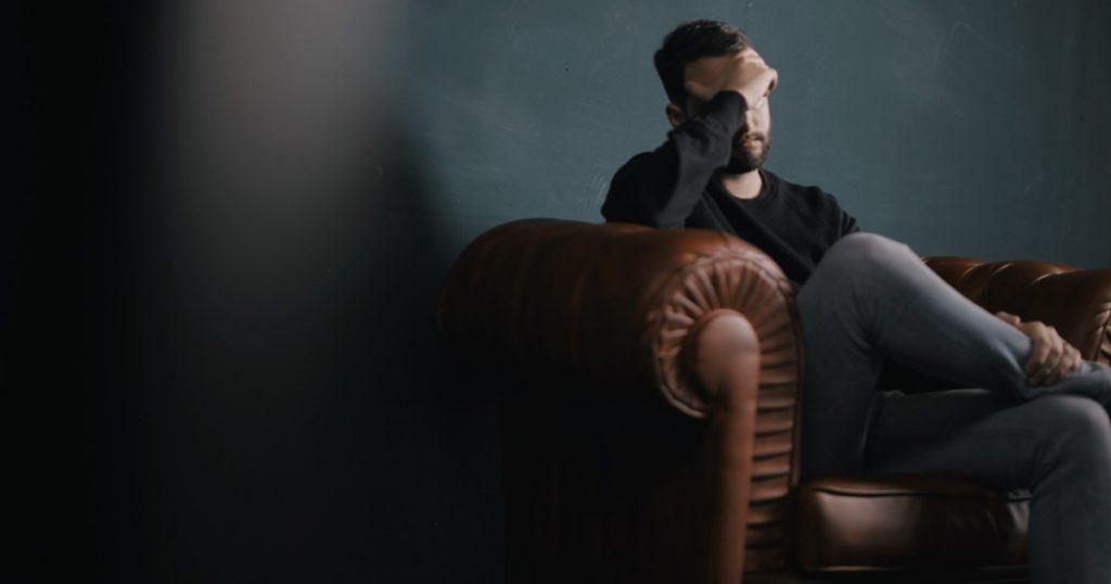 Mann sitzt gestresst auf einem Sessel und hält sich mit einer Hand die Stirn