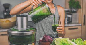 Eine Frau bereitet sich einen grünen Detox-Smoothie aus grünen Blattsalaten und Superfoods zu.