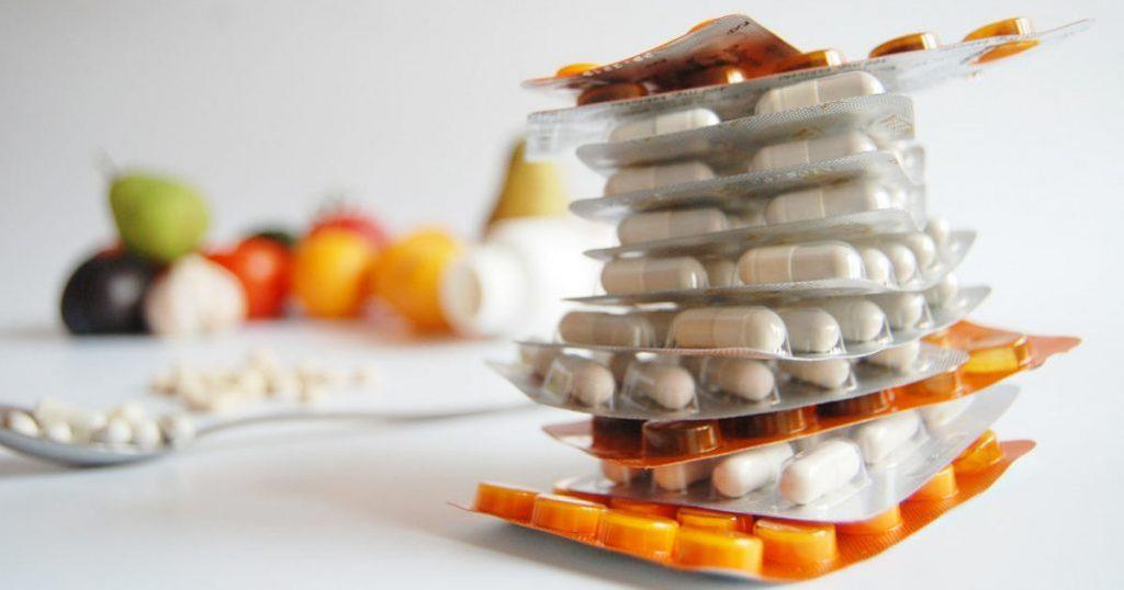 Im Vordergrund sind ein Stapel mit Tablettenpackungen abgebildet, während im Hintergrund ein Löffel mit ausgepackten Pillen und Obst im Hintergrund