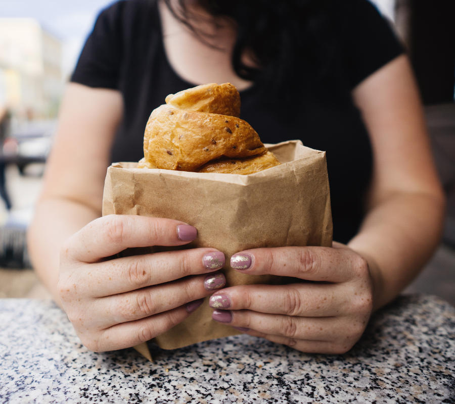 Eine übergewichtige Frau sitzt in einem Fast Food Reataurant und isst ein fettiges und ungesundes Gebäck