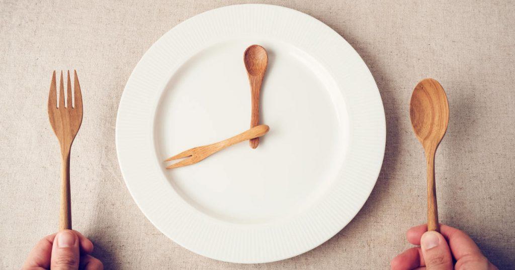 Abgebildet ist ein weißer runder Teller mit einem Holzlöffel und einer Holzgabel, die als Zeiger gemeinsam eine Uhrzeit legen.