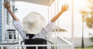 Frau mit Sonnenhut sitzt auf einem Balkon und streckt die Arme weit aus in Richtung Himmel und den letzten Sonnenstrahlen des Tages entgegen