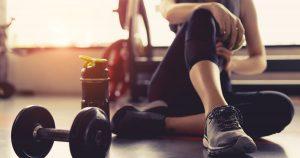 Frau sitzt in Sportklamotten neben einer Hantel auf dem Boden und ruht sich zwischen den Trainingssequenzen aus