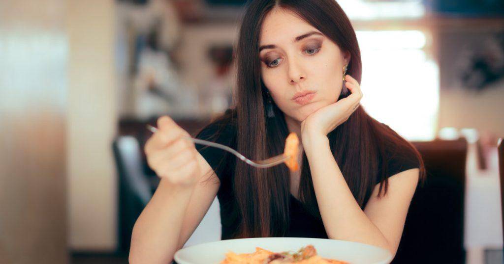 Zu sehen ist eine junge Frau, die ihr Essen, die Weizennudel auf der Gabel kritisch beäugt und hinterfragt, ob es gesund ist, diese zu essen