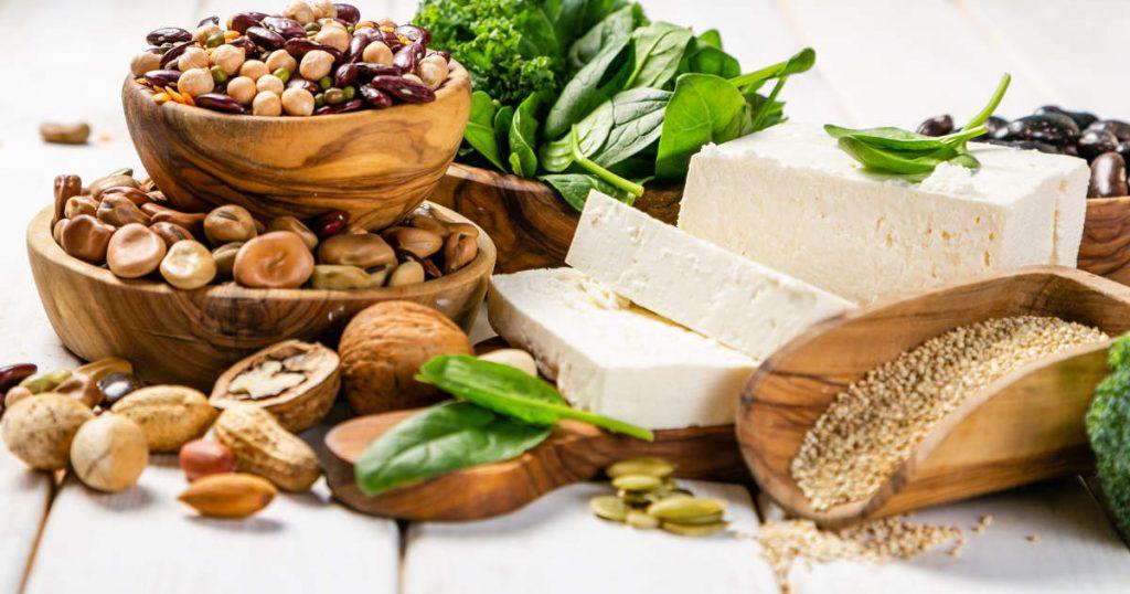 Pflanzliche Eiweißquellen wie Bohnen, Linsen, Nüsse, Samen und Tofu sind auf einem Tisch drapiert. Dazwischen liegen auch frische Kräuter