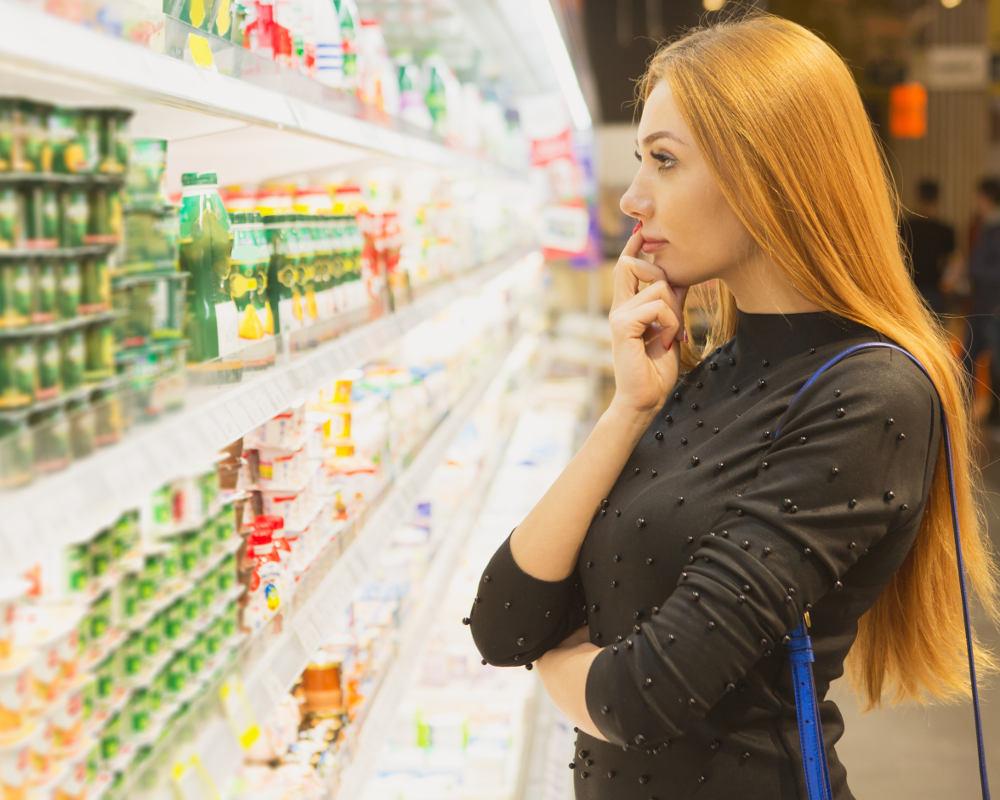 Eine Frau mit langen rötlich, blonden Haaren steht fragend vor einem vollen Supermarktregal und überlegt, was sie kaufen könnte