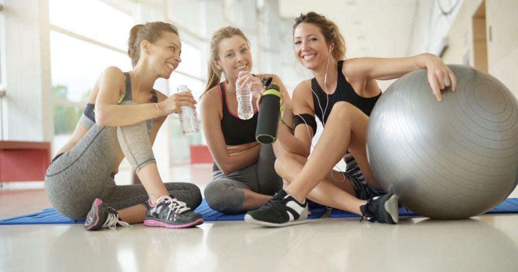 Drei junge Frauen machen gemeinsam Sport im Fitnessstudio