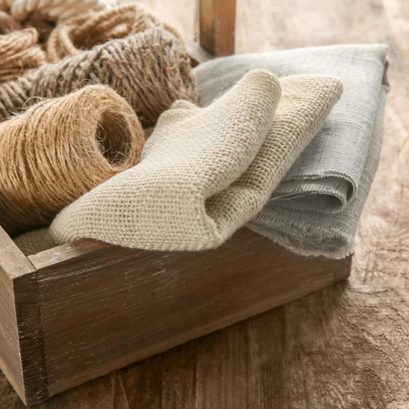 Dargestellt sind Stoffe und Garne aus Hanf in einer offenen Holztruhe