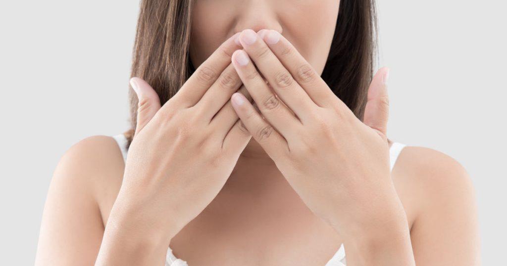 Eine Frau hält sich die Hand vor den Mund, da sie Mundgeruch hat und sich schämt