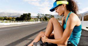 Eine Läuferin sitzt auf dem Boden und hält sich schmerzverzerrt ihren Fuß