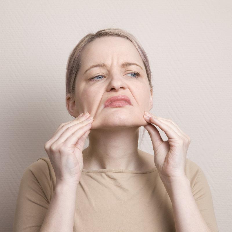 Eine Frau in ihren 50ern betrachtet ihre Falten, indem sie ihr Gesicht abtastet