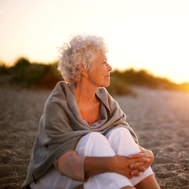 Eine ältere Frau sitzt glücklich und zufrieden am Strand im Sonnenuntergang