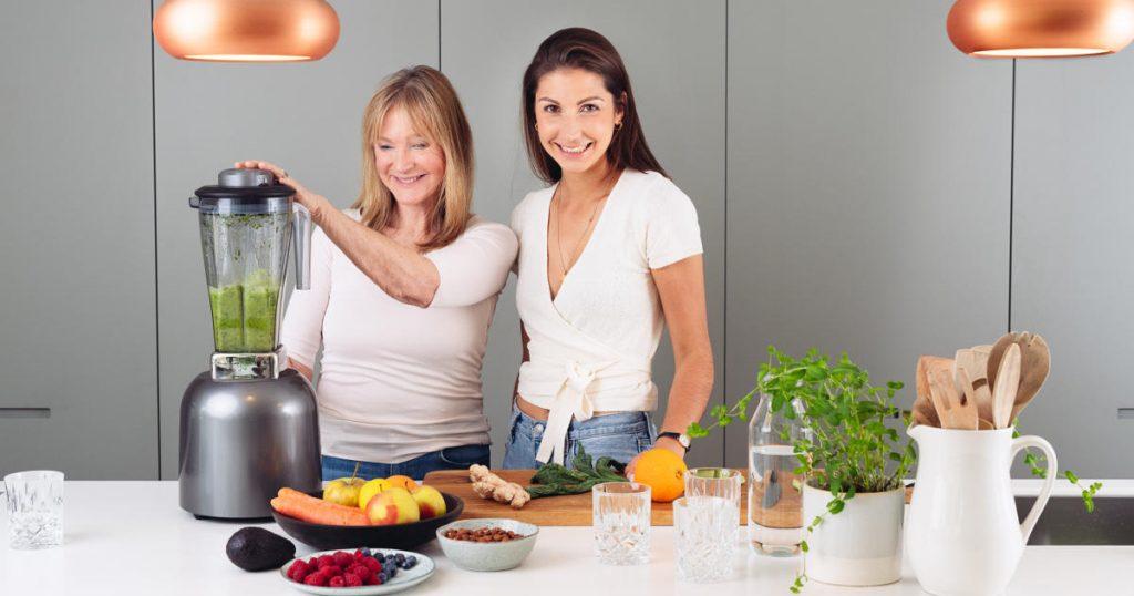 Mira und Petra gemeinsam in der Küche. Sie bereiten gemeinsam einen grünen Smoothie vor