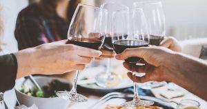 vier personen sitzen am Tisch und stoßen jeweils mit einem Glas Rotwein beim gemeinsamen Abendessen an