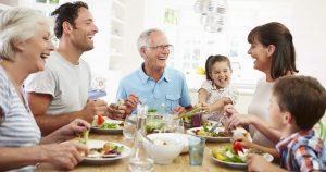 Mehrere Generationen einer Familie sitzen gemeinsam am Tisch und essen zusammen gesundes Essen