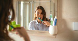 Eine junge Frau putzt sich die Zähne und schaut sich dabei im Spiegel an