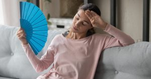 Eine Frau sitzt auf dem Sofa und fächelt sich mit einem Fächer Luft zu, da sie eine Hitzewallung hat