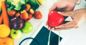 Abgebildet ist Obst und Gemüse,. Ein Arzt hält ein rotes Herz in der Hand, das symbolisiert, dass er sich für seine Patienten einsetzt.