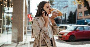 Eine beruflich beschäftigte Frau hält ihr Handy ans Ohr und beißt gleichzeitig in ein Sandwich