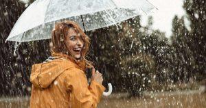Eine junge Frau steht in einer gelben Regenjacke und einem durchsichtigen Schirm im Regen und lacht