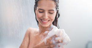Eine junge Frau steht unter der Dusche und wäscht ihre Haut mit einem Schwamm und schäumendem Duschgel