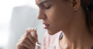 Eine junge Frau nimmt widerwillig eine Pille ein