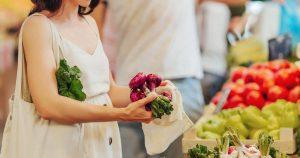 Eine junge Frau schaut sich auf dem Markt Obst und Gemüse an und kauft frische Produkte ein