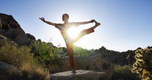 Ein Mann steht in einer Yogapose in der Natur und das Sonnenlicht erstrahlt hinter ihm
