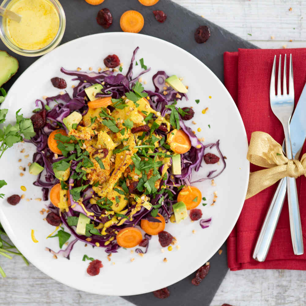 ein bunt zubereiteter Rotkohlsalat als Vorspeise zu Weihnachten. Daneben liegen Gabel und Messer auf einer Serviette mit Schleife drum herum