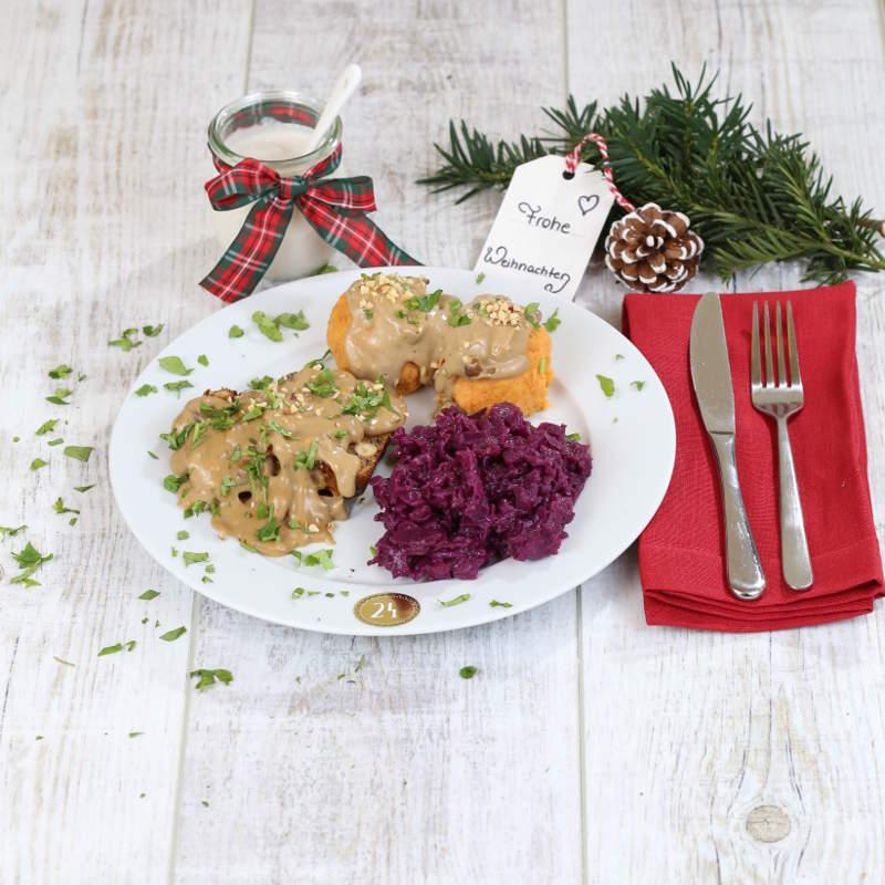 Ein Hauptgang mit Haselnussbraten, Süßkartoffelknödeln und Rotkohl ist schön auf einem Teller angerichtet. Daneben liegt Besteck und Weihnachtsdekoration