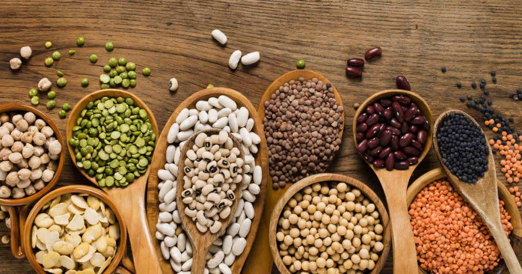 Verschiedene Bohnenarten und Linsen liegen auf kleinen Holzlöffeln und auf einem Tisch verteilt