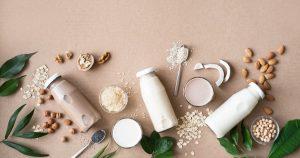 es liegen viele Nüsse, Getreidesorten und Glasflaschen mit jeweiliger Getreide-und Nussmilch auf einem Tisch