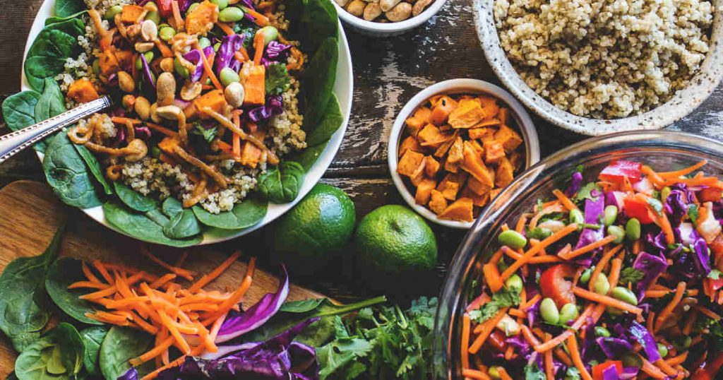 Viele verschiedene gesunde Lebensmittel sind auf einem Tisch abgebildet. Bunte Salate, Zitrusfrüchte und Hirse liegen nebeneinander.