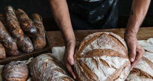 Ein Bäcker zeigt sein selbstgebackenes Brot. Neben ihm liegen einige Brotlaibe
