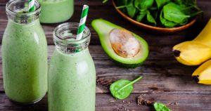 Grüne Smoothies in Smoothieflaschen mit Strohalm stehen auf einem Holztisch. Daneben liegen Bananen, eine halbe Avocado und Spinatblätter