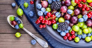 Ein großer Teller voller verschiedener Beeren steht auf einem Tisch. Abgebildet sind Johannisbeeren, Brombeeren, Stachelbeeren und Blaubeeren