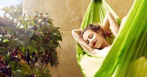 Eine junge Frau liegt in einer grünen Hängematte auf ihrem Balkon und sonnt sich.