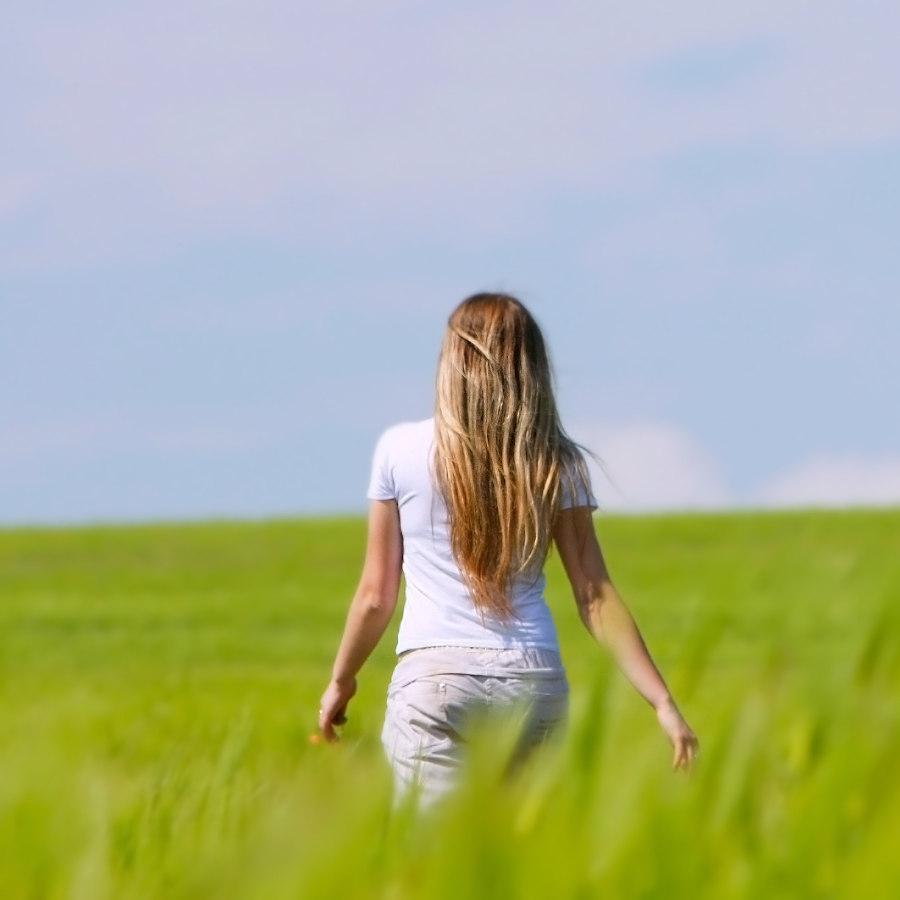 Eine Frau mit langen blonden Haaren geht entspannt über ein Feld mit hohem Gras